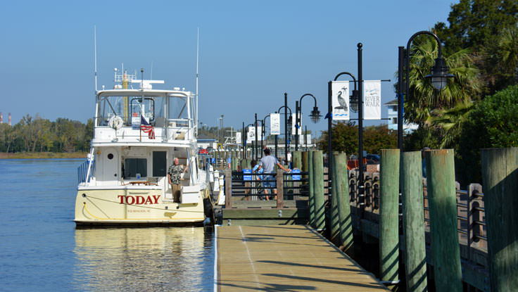 A boat docked at the Riverwalk in Wilmington, NC